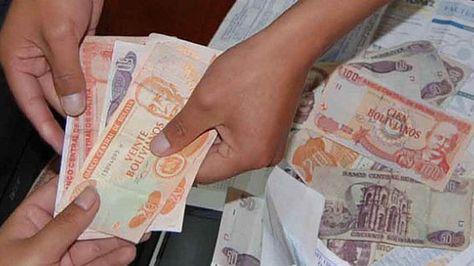 Unas personas intercambian dinero. Foto: https://www.cfb.org.bo