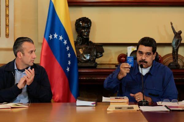 El presidente venezolano Nicolas Maduro muestra una copia de la constitución este jueves en el Palacio de Miraflores. A su derecha, el vice presidente Tareck El Aissami (Reuters)