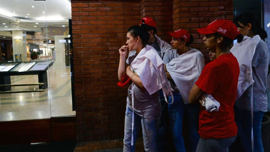 ocals stand next to a shopping center following an explosion inside the building which -according to authorities, left one dead and eleven injured, in Bogota, Colombia, on June 17, 2017. / AFP PHOTO / Raul Arboleda (Photo credit should read RAUL ARBOLEDA/AFP/Getty Images)
