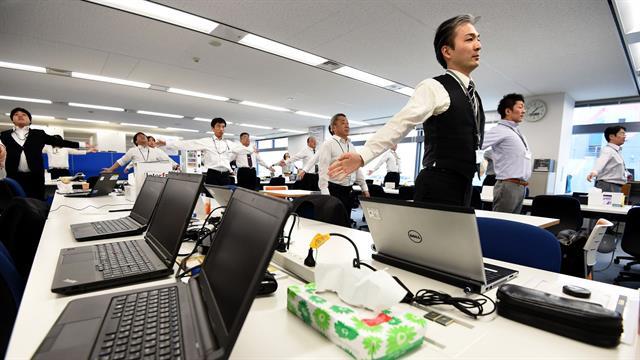 Los empleados de una empresa de tecnología mientras hacen ejercicios en sus oficina, después de la hora del almuerzo en Tokio.