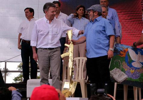 El presidente de Colombia, Juan Manuel Santos (izq.), conversa con el máximo líder de las FARC, Rodrigo Londoño, alias Timochenko, durante la ceremonia de dejación de armas. Foto: EFE