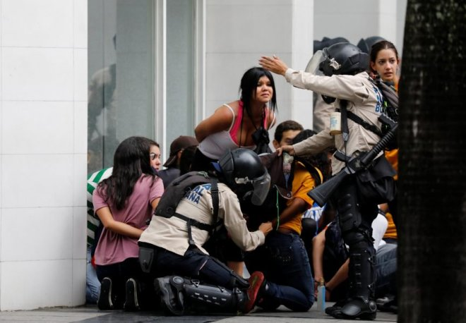 Police detain protesters during a rally against Venezuela
