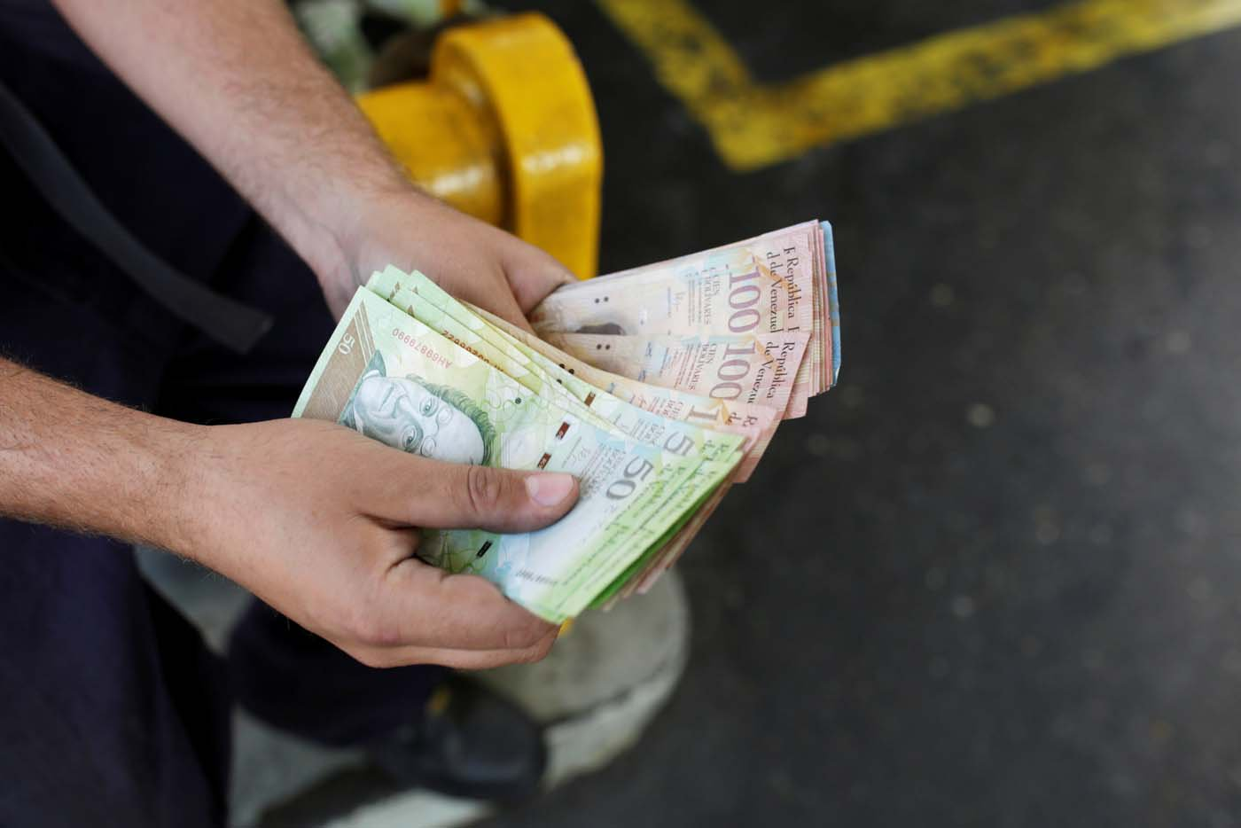 A worker counts Venezuelan bolivar notes at a gas station of Venezuelan state oil company PDVSA in Caracas, Venezuela March 21, 2017. REUTERS/Marco Bello