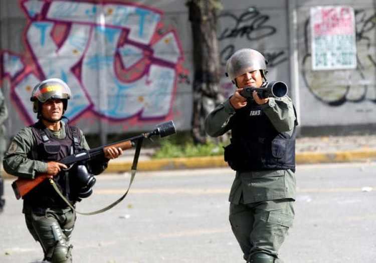 Un miembro de la Guardia Nacional Bolivariana apunta su arma contra los manifestantes. (REUTERS/Andres Martinez Casares)
