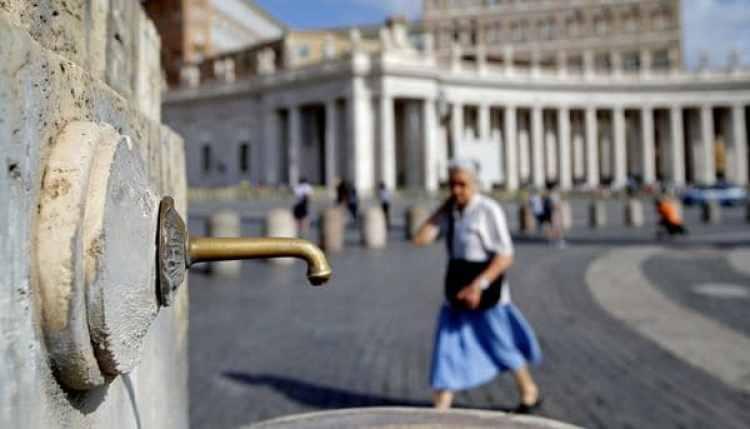 Una mujer camina junto a una fuente en la plaza San Pedro (Reuters)