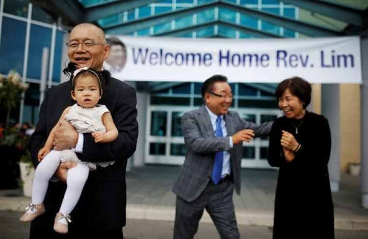 Hyeon Soo Lim carga en brazo a su nieto mientras deja la Iglesia Presbiteriana de la Luzen Mississauga, Ontario, el domingo (Reuters)