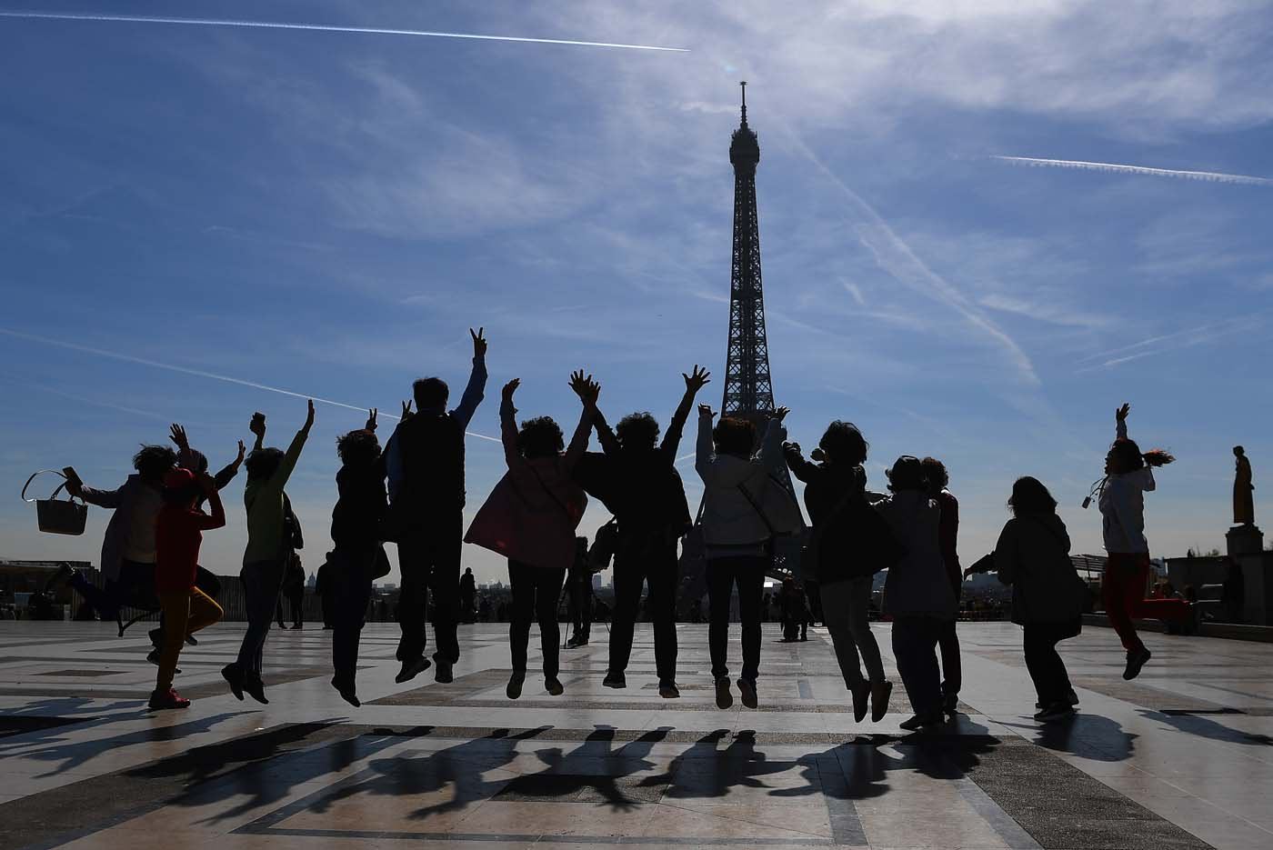 (FILES) This file photo taken on March 30, 2017 shows tourists jumping as they pose for a family photo on the Esplanade du Trocadero near the Eiffel Tower in Paris. After a decline in 2016 due to the terror attacks in Paris and Nice, tourism in Paris and Ile de France is in much better shape in the first half of 2017, with 1,5 million tourists and 3,3 million overnight stays more than a year ago. / AFP PHOTO / GABRIEL BOUYS