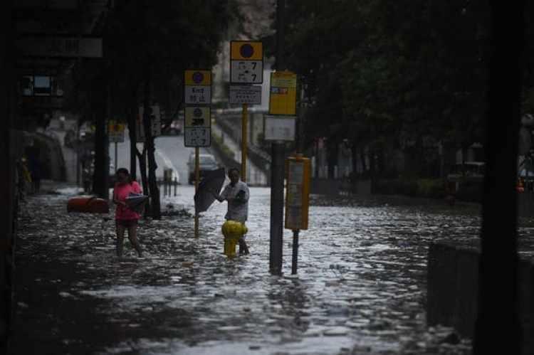 Residentes caminan por las calles inundadas en Heng Fa Chuen, Hong Kong (AFP)