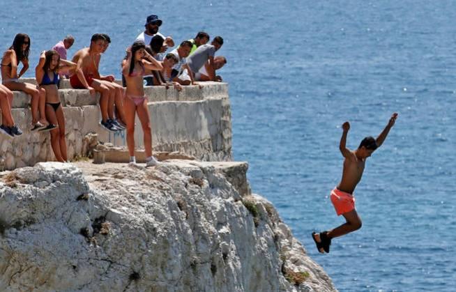 Adolescentes se lanzan al mar en Marsella. (Reuters)