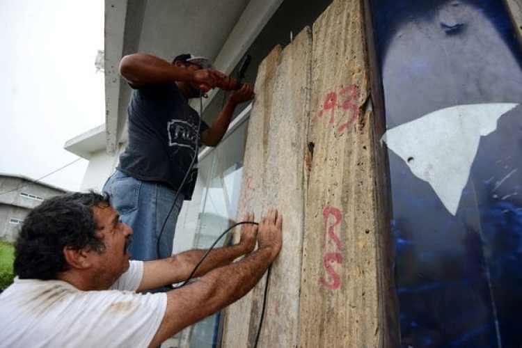 Dos hombres cubren las ventanas de una casa en Veracruz. (REUTERS/Oscar Martinez)