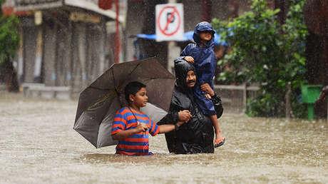 Un hombre camina con sus dos hijos a través del agua en Bombay, en la India