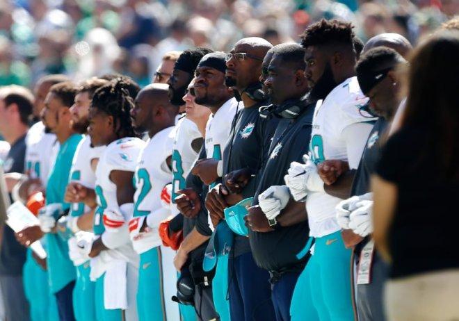 Los Miami Dolphins cantaron el himno nacional estadounidense entrelazados, antes del juego contra los New York Jets en el MetLife Stadium. Rich Schultz/Getty Images/AFP