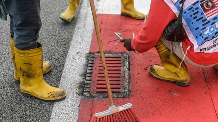 Los empleados trabajando sobre la alcantarilla que produjo el accidente de Romain Grosjean (AFP)