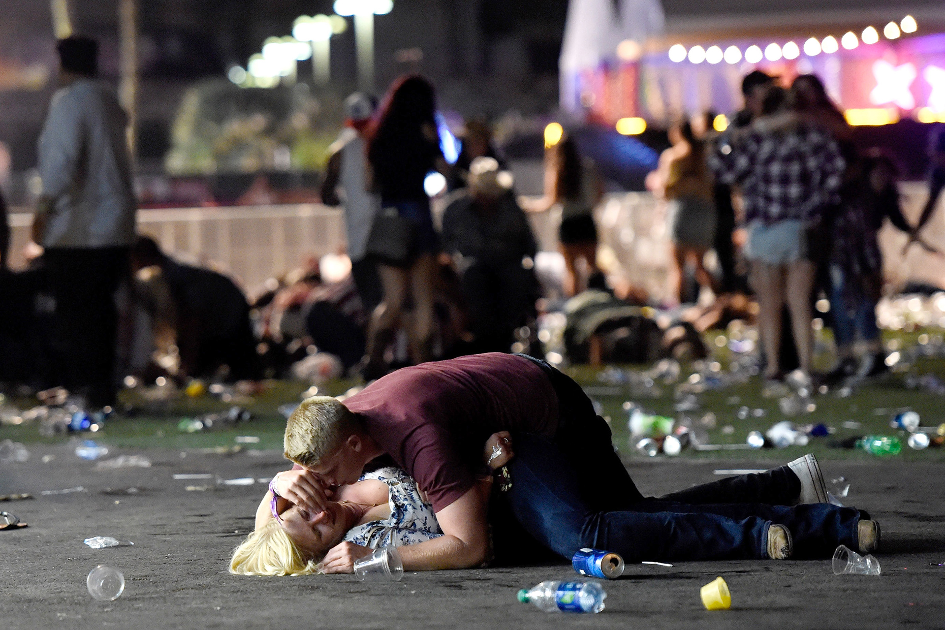 Un hombre acaricia el cuerpo de una mujer que ha quedado en el piso rodeada de bausra, instantes después del ataque(David Becker/Getty Images/AFP)