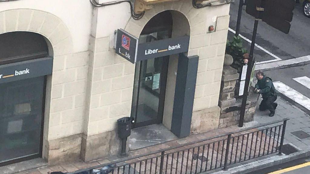 Foto de la sucursal de Liberbank, con el atracador detenido en el suelo.