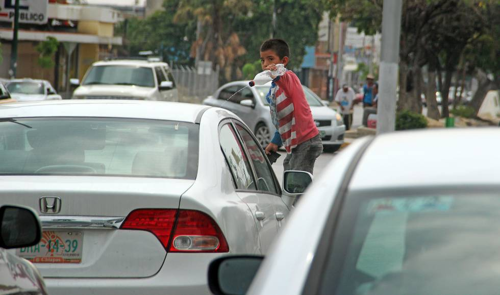 Un niño de Tuxtla Gutiérrez (Chiapas) limpia el parabrisas de un automóvil.