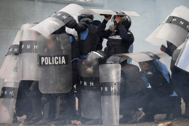 La policía antidisturbios se cubre ante la arremetida de los manifestantes. (REUTERS/Edgard Garrido)