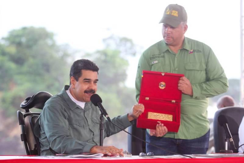 El presidente venezolano, Nicolás Maduro, muestra un lingote de oro durante un acto.