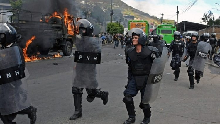 Oficiales se movilizan mientras arde un vehículo policial, en Tegucigalpa (AFP)