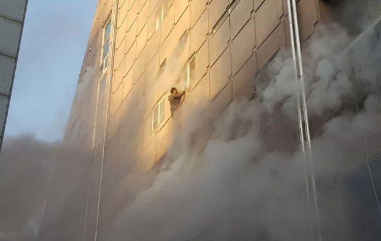 Un hombre intenta lanzarse al vacío y salvarse de las llamas.