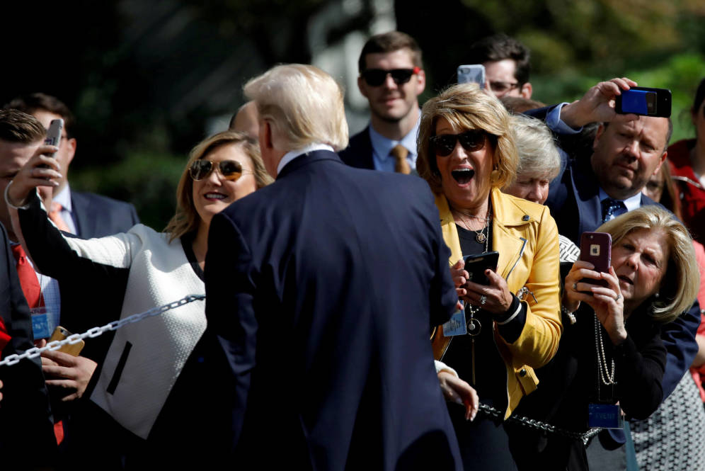 Foto: Visitors react as U.S. President Donald Trump poses for a picture as he departs the Oval Office of the White House for Dallas, in Washington D.C.