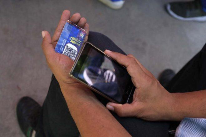 """Una tarjeta de identificación es revisada en un """"Punto Rojo"""", un área establecida por el partido del presidente Nicolás Maduro para verificar que las personas emitan sus votos, durante las elecciones presidenciales en Caracas, Venezuela, el 20 de mayo de 2018. REUTERS / Marco Bello"""