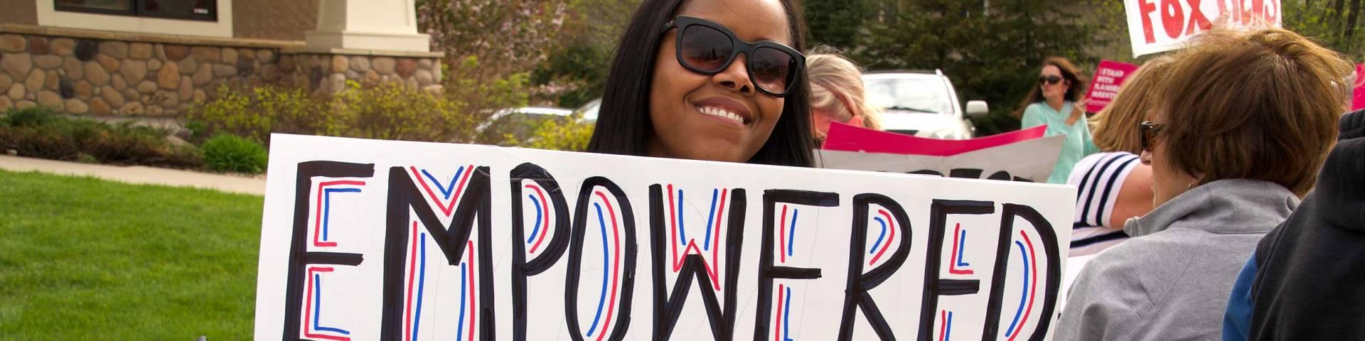 Renita closeup with sign.