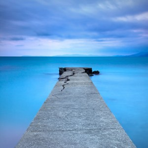 Broken concrete pier or jetty and rocks on a blue sea. Hills on background. Long exposure photography.
