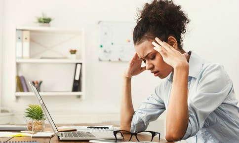 Woman experiencing a headache at work