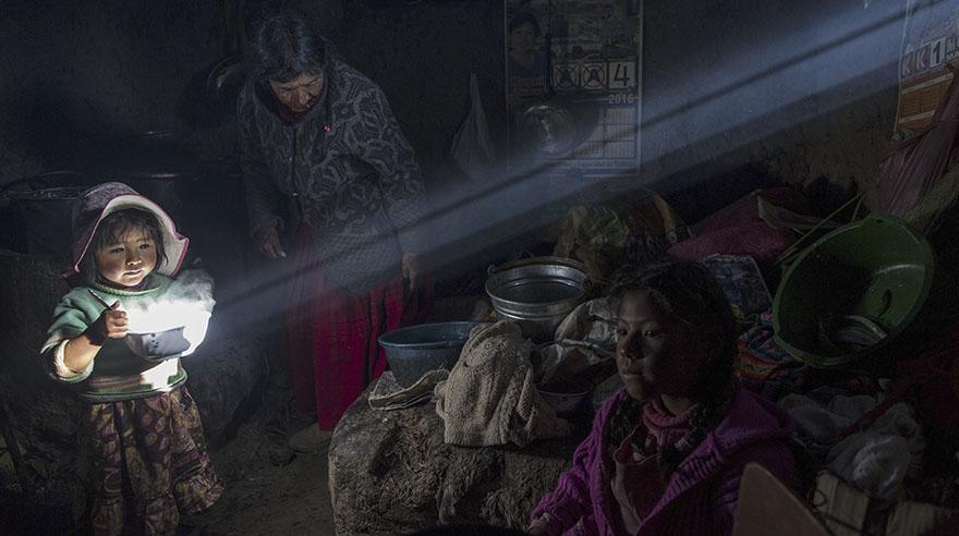 Un niño sostiene un plato de comida caliente mientras la familia Ávila almuerza en su casa en Coata, un pequeño pueblo a orillas del lago Titicaca(AP/Rodrigo Abd)