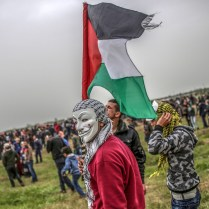 epaselect epa07473796 A Palestinian protester wearing a Fawkes Guy masks takes part during the protests near the border between Israel and Gaza Strip, eastern Gaza Strip, 30 March 2019. Two Palestinian protesters were shot dead by Israeli snipers and more than 50 others wounded during the clashes eastern Gaza Strip. Palestinian protesters plan to call for the right of Palestinian refugees across the Middle East to return to homes they fled in the war surrounding the 1948 creation of Israel. EPA-EFE/MOHAMMED SABER