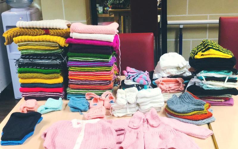 Elderly women knit scarves, hats and socks for children's home