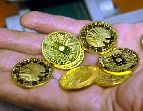 Gold edges up on softer dollar, Fed stimulus bets