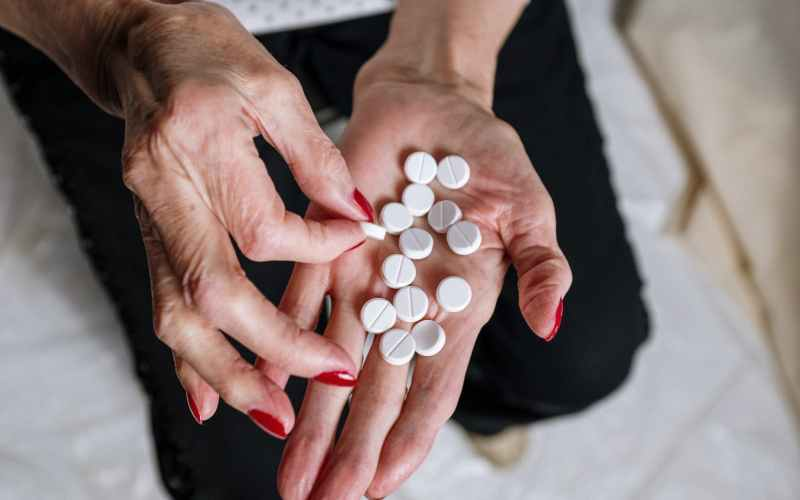 person holding white round medication pill