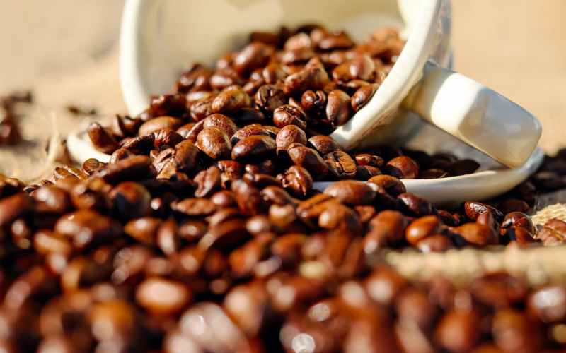 shallow focus of coffee beans on white ceramic cup