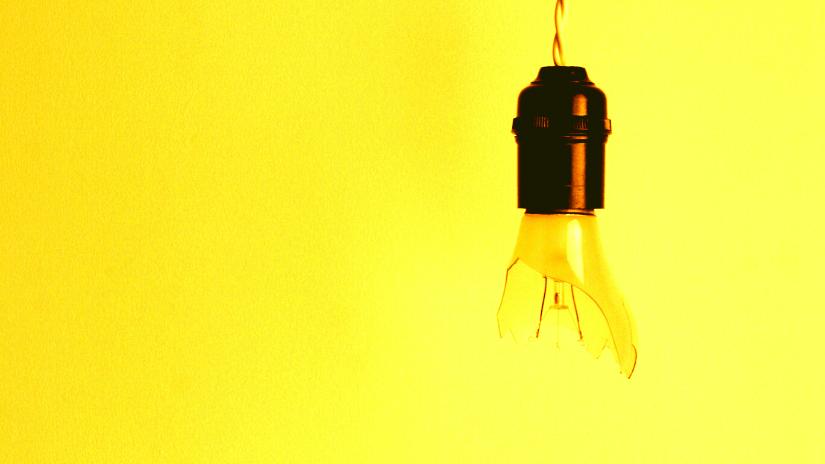 Broken lightbulb on yellow background to illustrate online traffic not converting.