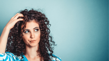 Woman scratching her head looking confused against a blue background.