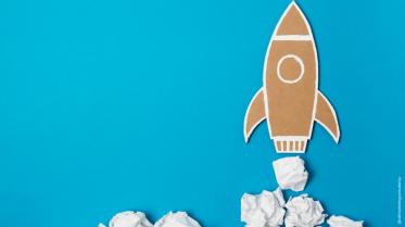 Illustration of a rocket taking off on a blue background