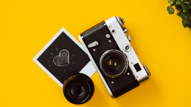 Camera and polaroid on a yellow background to signify optimising images for search engines.