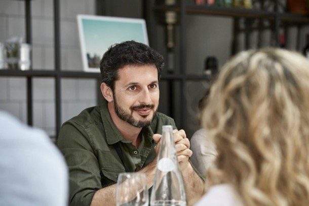 رجل جالس على الطاولة مع آخرين