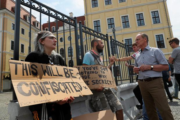 Protesters stand outside the Hotel Taschenbergpalais Kempinski Dresden, venue of the 2016 Bilderberg Group conference, on June 9, 2016 in Dresden, Germany. (Photo by Sean Gallup/Getty Images)