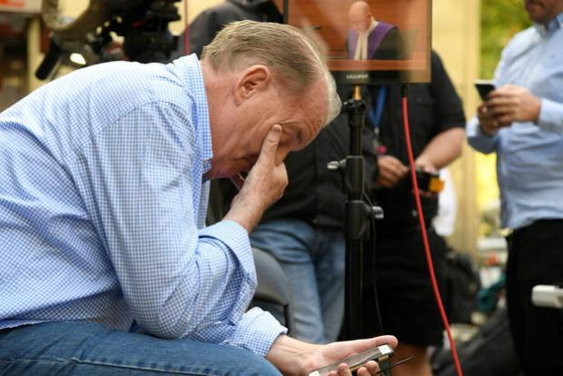 A member of the public reacts to Pell's sentence. Image: AP Photo/Andy Brownbill