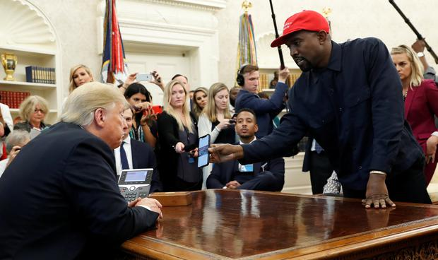 Rapper Kanye West shows President Donald Trump a picture on his mobile phone of what he described as a hydrogen powered airplane that should replace Air Force One REUTERS/Kevin Lamarque