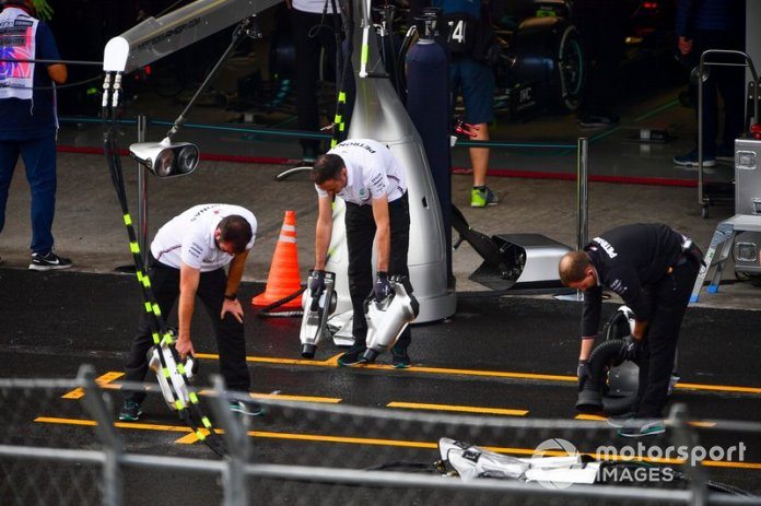 Los mecánicos de Mercedes intentan secar el asfalto fuera de su garaje