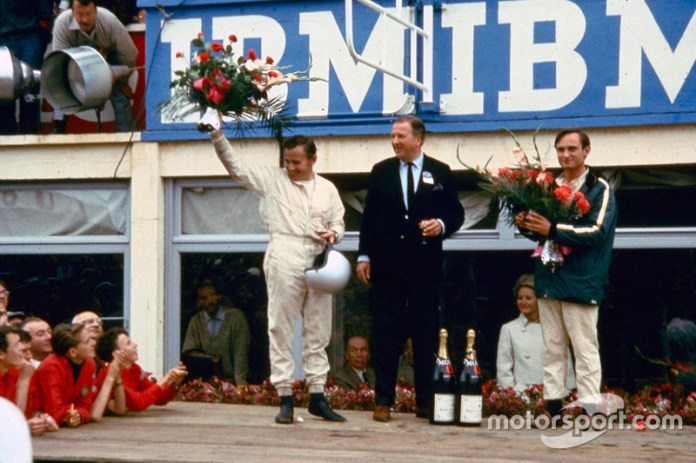 From left: Henry Ford II, Bruce McLaren and Chris Amon on the victory podium after 24 hours of Le Mans 1966