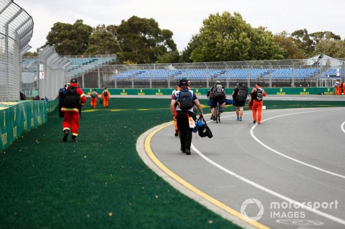 Los oficiales de pista dejan sus posiciones tras la noticia de que el evento es cancelado