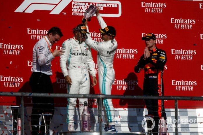 Valtteri Bottas, Mercedes AMG F1, 1ª posición, derrama Champagne sobre la cabeza del campeón del mundo de 2019 Lewis Hamilton, Mercedes AMG F1, 2ª posición, en el podio
