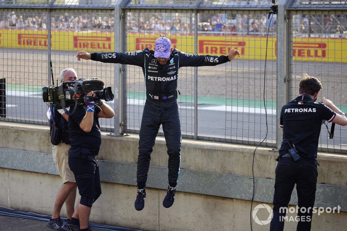 Pole man Lewis Hamilton, Mercedes, jumps off the fence
