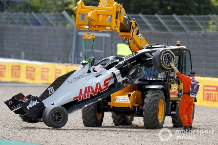 Una grúa retira el monoplaza de Kevin Magnussen, Haas VF-20