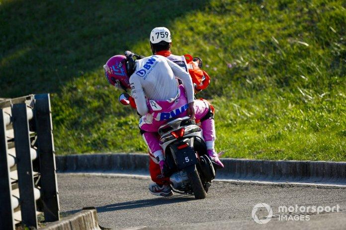 Lance Stroll, Racing Point en la parte trasera de un Scooter después de un accidente